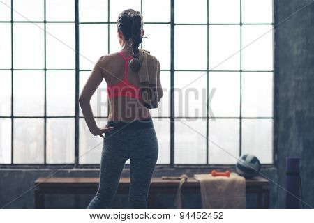 Rear View Of Woman Holding Towel Looking Out Window In Loft Gym
