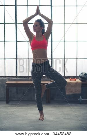 Fit Woman Doing Tree Pose In Loft Gym