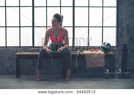 Woman Sitting On Bench In Loft Gym Listening To Music On Device