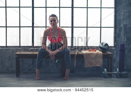 Woman Sitting On Bench By Window In Loft Gym Listening To Music