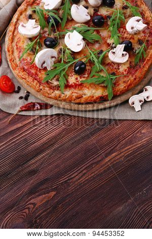 Tasty pizza with vegetables and arugula on table close up
