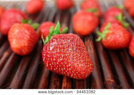 Ripe strawberries on bamboo sticks background