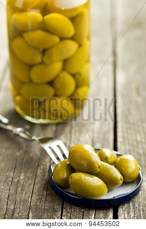 pickled green olives on old table