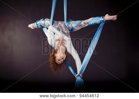 Flexible girl doing exercise on aerial tissues