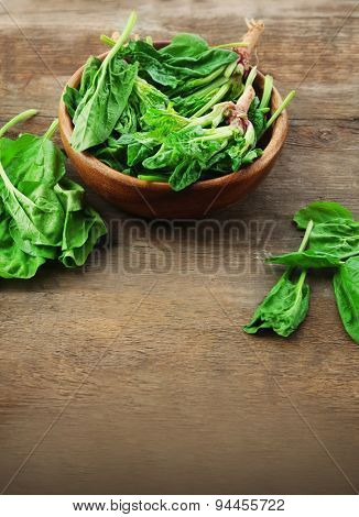 Bowl of fresh spinach leaves on wooden background