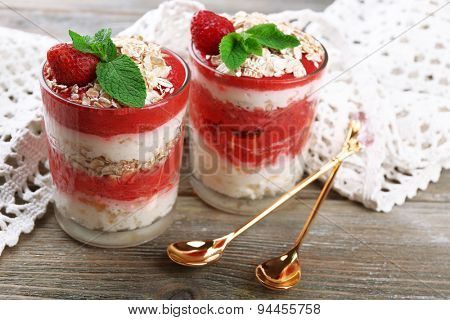 Dessert with fresh strawberry, cream and granola, on color wooden table background