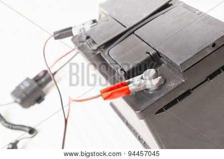 Charging old car battery at workshop