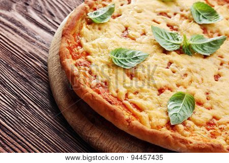 Cheese pizza with basil on table close up