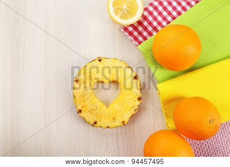 Pineapple slice with cut in shape of heart and different fruits on table close up