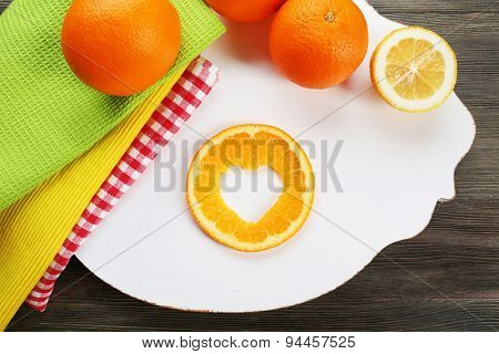 Orange slice with cut in shape of heart on table close up