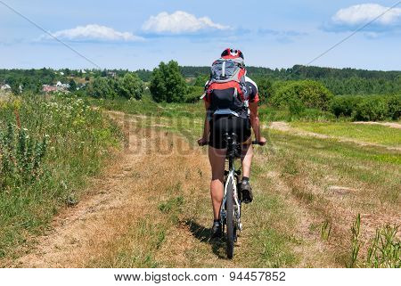 Cyclist riding a mountain bike in direction of the village