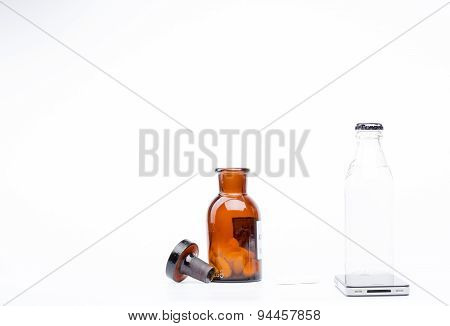 Bottle of water, a glass medicine bottle and white pills