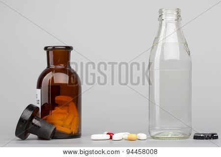 Bottle of water, a glass medicine bottle and pills