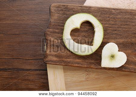 Apple slice with cut in shape of heart on wooden background