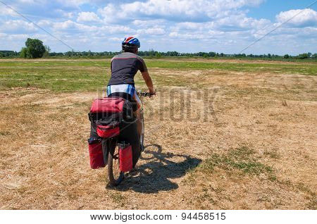 Active man on a mountain bike rides along the grass clippings