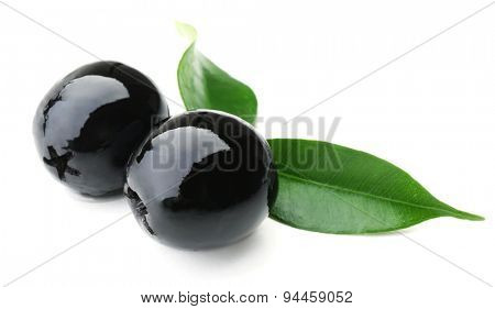 Black olives with green leaves isolated on white