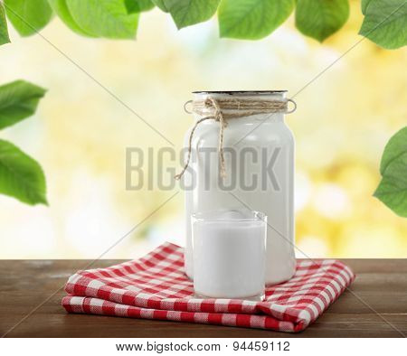 Retro can for milk and glass of milk on wooden table, on nature  background