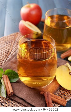 Glasses of apple juice on wooden table, closeup