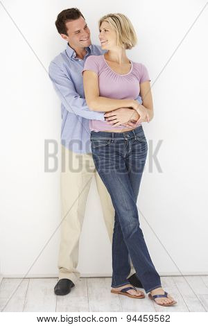 Studio Portrait Of Romantic Couple Embracing Against White Background