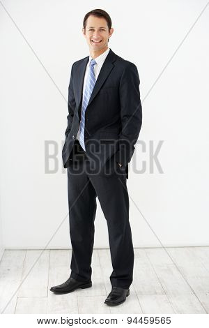 Studio Portrait Of Businessman Standing Against White Background