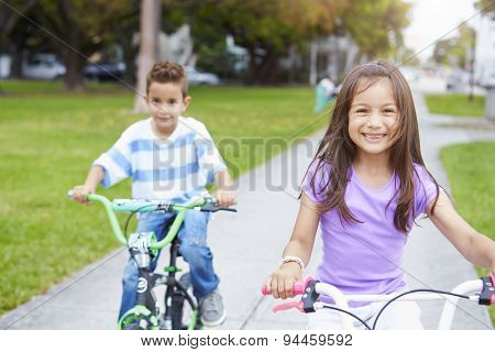 Two Hispanic Children Riding Bikes In Park