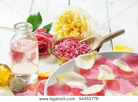 Rose petals in bowl of water, bath salt and bottle with oil, flowers in background