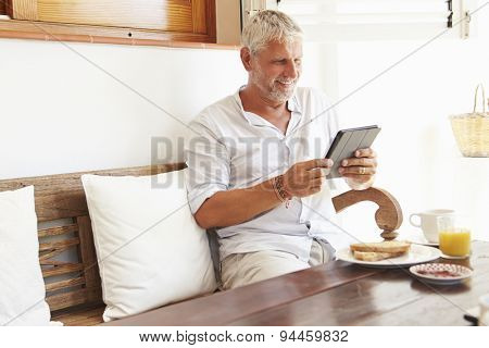 Mature Man Sitting At Breakfast Table Using Digital Tablet