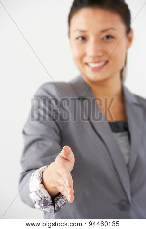 Studio Portrait Of Businesswoman Reaching Out To Shake Hands