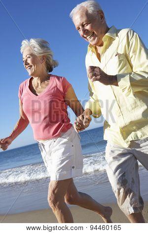 Senior Couple Running Along Beach Together