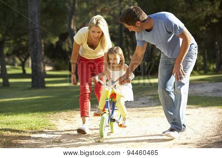 Parents Teaching Daughter To Ride Bike