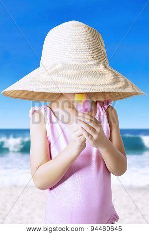 Child With Hat Enjoy Ice Cream At Coast
