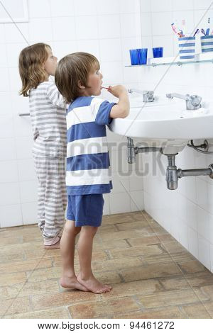 Boy And Girl In Bathroom Brushing Teeth