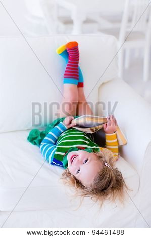 Little Girl Reading A Book On A White Couch