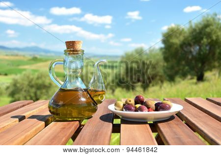 Olive oil and olives on the wooden table against Tuscan landscape. Italy