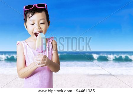 Excited Girl Eats Ice Cream At Shore