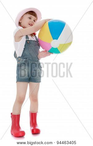 Nice girl in rubber boots and shorts holding a ball