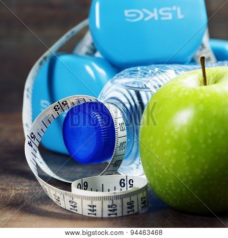 Green apple, dumbbells, water and measuring tape. Health, sport and diet concept