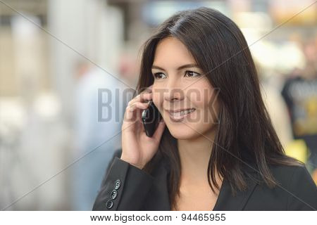 Attractive Woman Smiling As She Chats On A Mobile