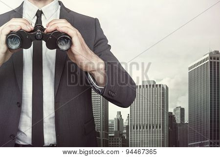 Businessman holding binoculars on cityscape background