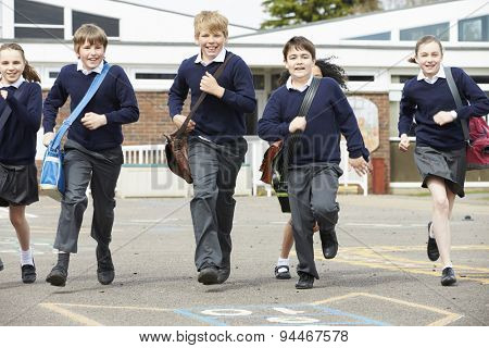 Group Of Elementary School Pupils Running In Playground