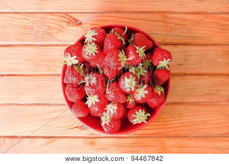 A Bowl Full Of Strawberries In The Middle Of The Table, Top View