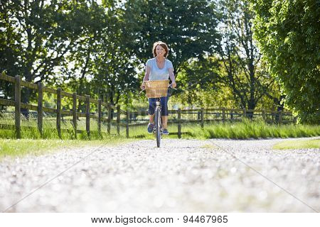 Attractive Mature Woman Riding Bike Along Country Lane