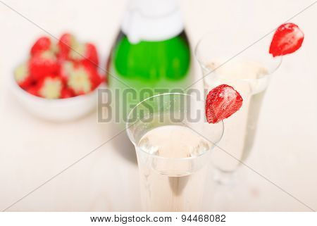 Two Glasses Of Champagne With Sliced Strawberries, Against A Bottle Of Champagne And Strawberries