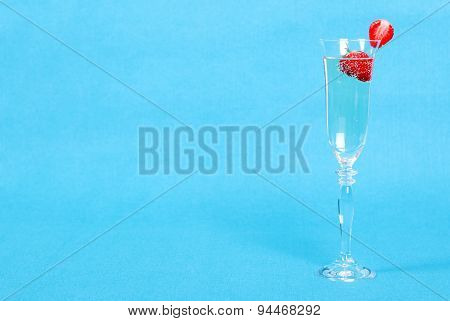 A Glass Of Champagne And Strawberries On The Blue Background, Side View, Left Space For Text