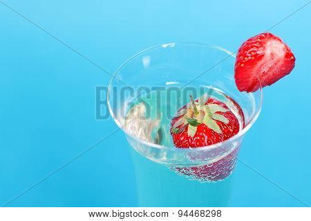 Glass With Champagne And Strawberries, Close-up On A Blue Background