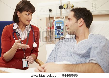 Female Doctor Sitting By Male Patient's Bed In Hospital