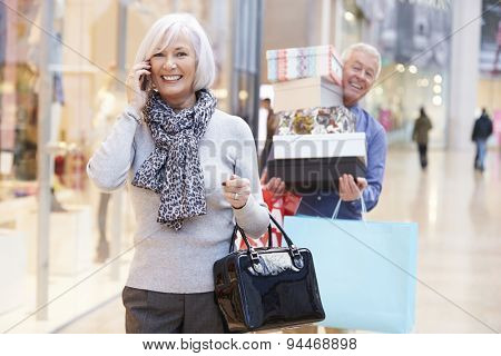 Senior Woman Shopping In Mall As Husband Carries Boxes