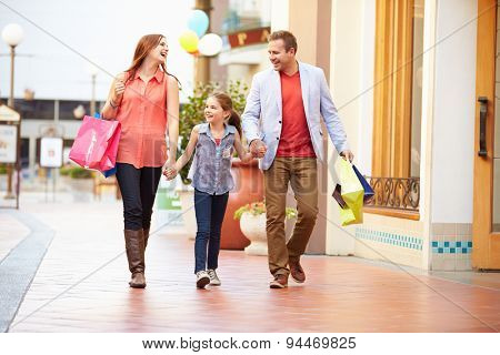 Family Walking Through Mall With Shopping Bags