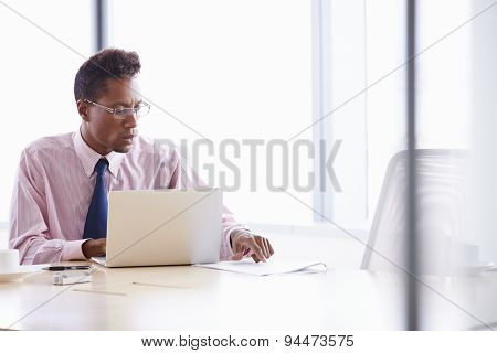 Businessman Working On Laptop At Boardroom Table