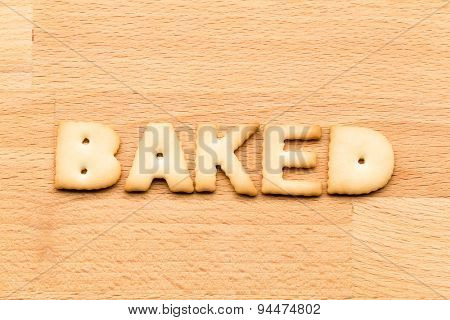 Word baked biscuit over the wooden background